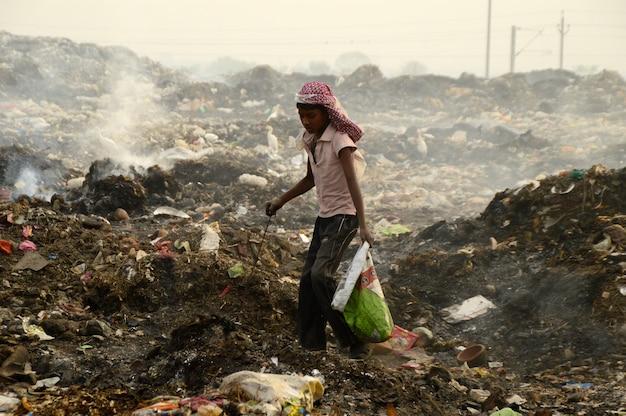 ぼろきれピッカーがインドのゴミの土地と大気汚染でリサイクル可能な材料を探す