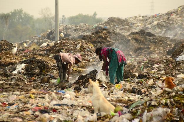 Сборщики тряпок ищут перерабатываемый материал на мусорной земле и загрязнение воздуха в индии