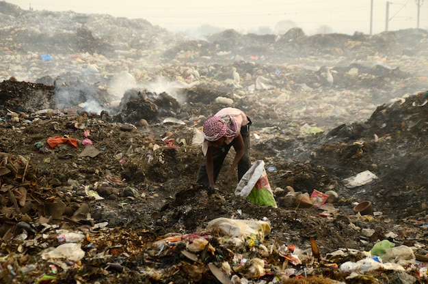 Rag pickers search for recyclable material in the garbage land and air pollution in india