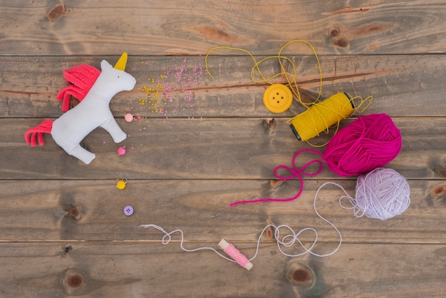 Rag unicorn horse with yarn; pink and purple spool with thread and button on wooden desk
