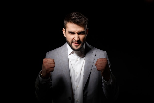 Rage young successful businessman angering over black wall
