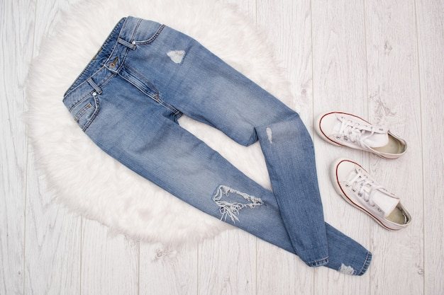 Ragged blue jeans and white sneakers on white fur. fashionable concept