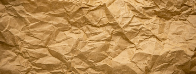 Ragged crumpled brown kraft paper texture banner background