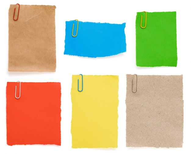 Ragged note paper and clip isolated on white background