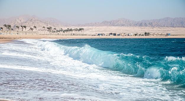 Бушующее море с пенистыми волнами в солнечную погоду. вид на побережье с горами.