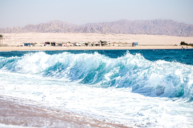 Raging sea with foamy waves in sunny weather. view of the coast with mountains.