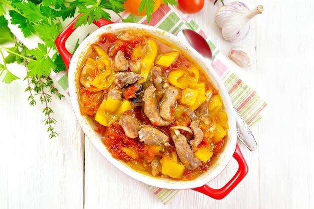 七面鳥の肉、トマト、黄パプリカ、タマネギのぼろぼろで、上に木の板の背景にナプキンのブレイザーにソースを添えた