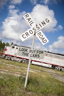 Rail road crossing sign on the train station outdoors on sky background.