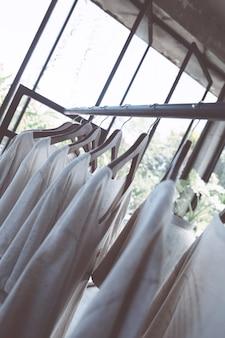 Рейка с белыми футболками на вешалках в магазине. повседневная летняя одежда