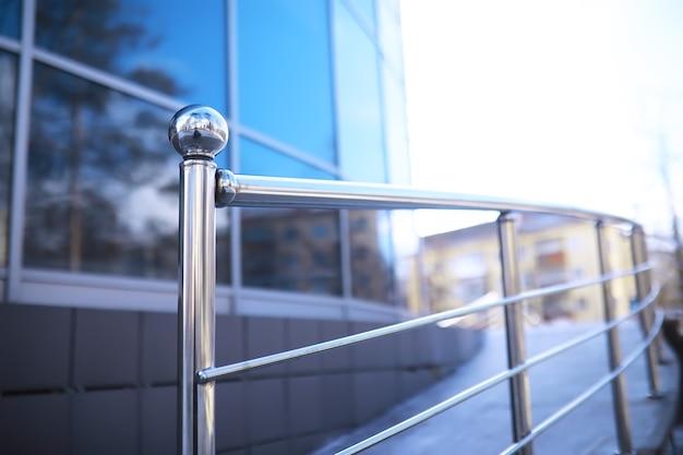 유리와 스테인리스 스틸로 만든 난간. 현대적인 인테리어의 계단입니다. 유리 난간. 현대적인 건물로 이어지는 계단의 낮은 각도 보기.
