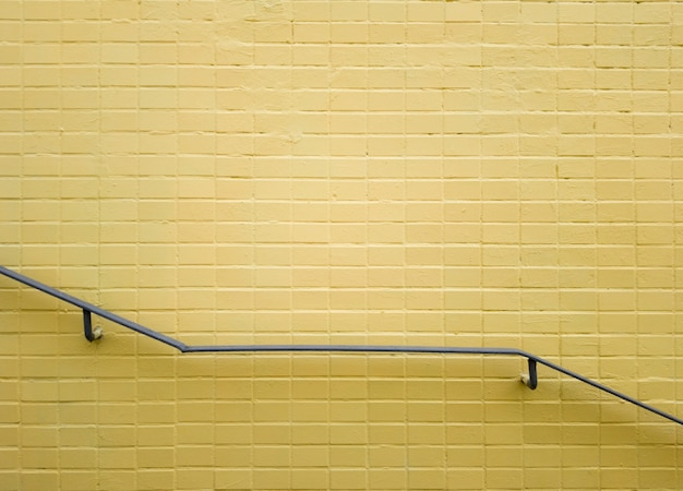 노란색 벽돌 벽 근처에 회색 금속 난간. 노란색 배경, 벽돌 질감입니다. 미니멀리즘. 복사 공간