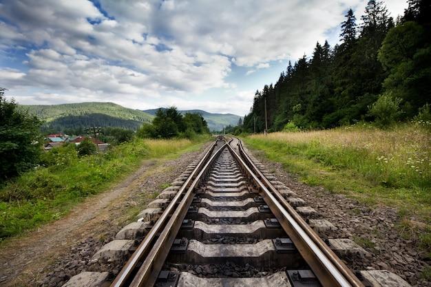 Железная дорога против гор и красивого неба, недалеко от леса.
