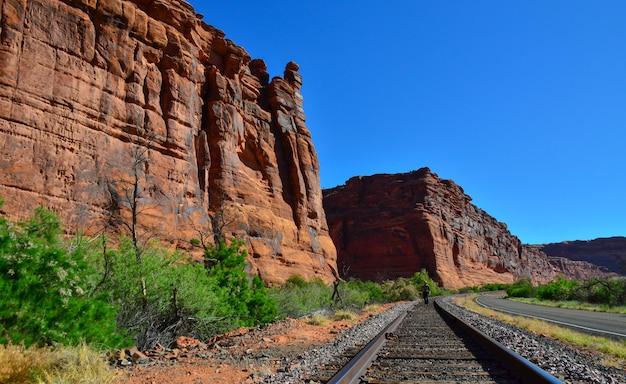 The railroad runs along the red mountains in utah, in the distance is a man between the rails. utah usa