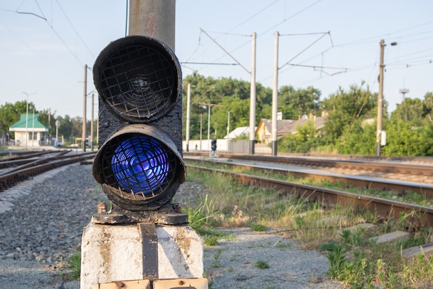 Railroad signal with blue light with a railroad junction. train blue traffic light prohibiting traffic. railway junction. heavy industry. railways. the traffic light on the railway is lit in blue.