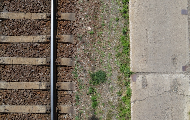 Вид сверху железной дороги, плоская планировка. часть пути для поездов. аэрофотоснимок железной дороги с дрона. фон с пространством для текста. блестящие железные рельсы и бетонные шпалы.