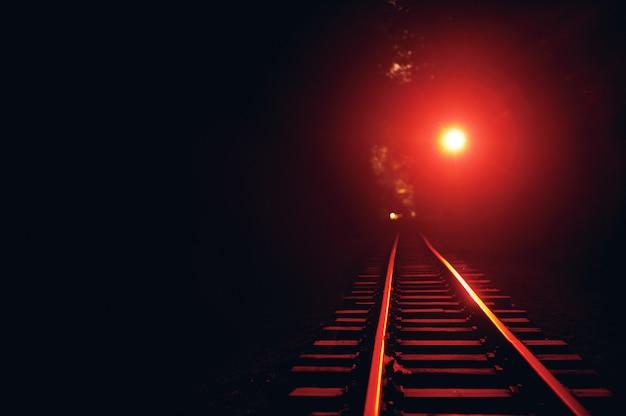 Железнодорожный путь ночью. красный свет включен.