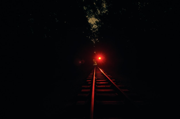 Railroad track at night. red light is on.