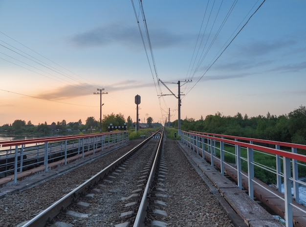 Railroad tracks on the bridge by the countryside in the evening