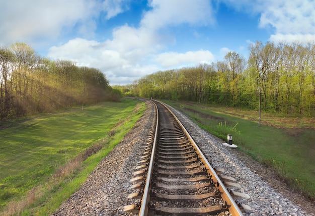 나무의 가지를 통해 빛나는 아침 햇살과 철도 트랙. 이른 봄, 길을 따라 자연과 푸른 하늘에 구름.