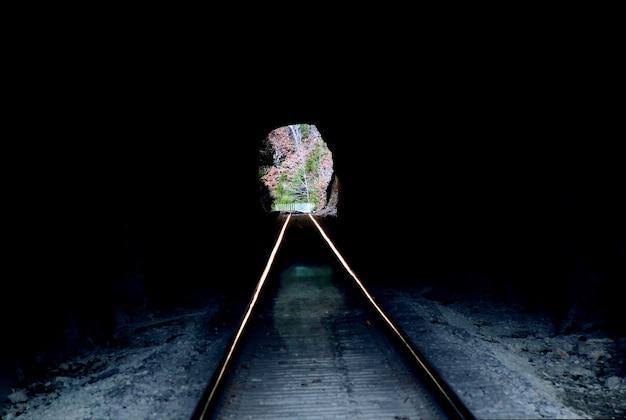 鉄道トンネルは暗い日光の下で外を見ています。トンネルの開口部から遠くまで走る線路。森と木。