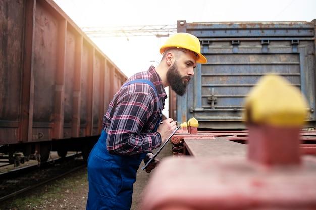 貨物コンテナを輸送するためのスペースをチェックする鉄道労働者