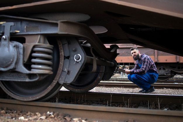 Railroad worker inspecting wheels and brakes of the freight train