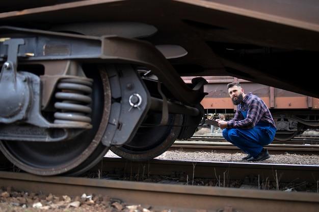 Operaio ferroviario che ispeziona ruote e freni del treno merci