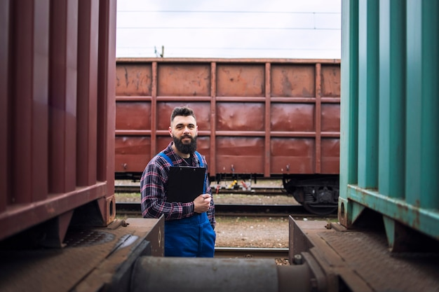 Железнодорожник стоит у поездов и смотрит в камеру на станции
