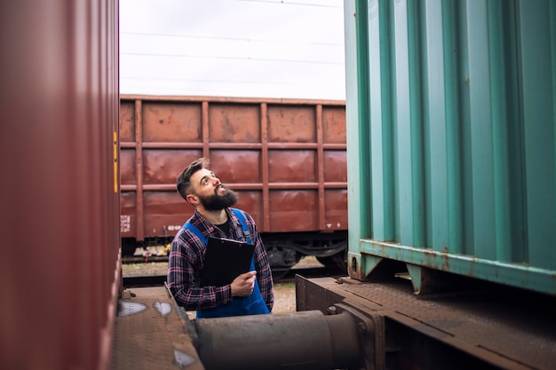 Railroad worker supervisor inspecting shipping cargo container at freight train station