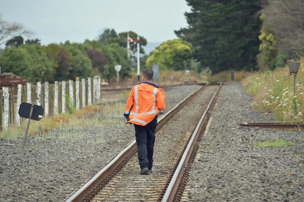 線路の間を歩いている鉄道労働者