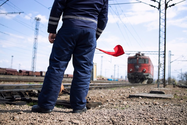 Railroader or switchman at station waving with red flag to the incoming train and signalizing locomotive to slow down or stop.