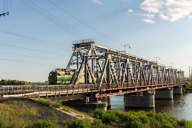 Railway bridge through the river volga and freight train is movi