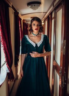 Путешествие по железной дороге, женщина в ретро платье, старинный интерьер купе поезда.