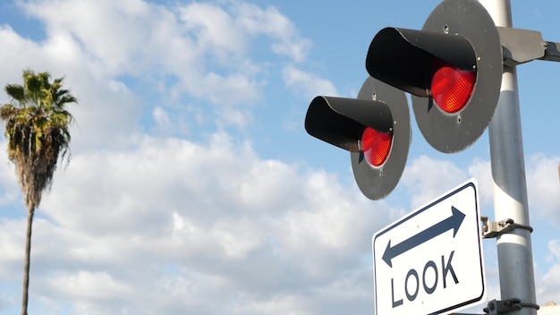 Railway level crossing signal in usa. look notice and red traffic light on railroad in california.