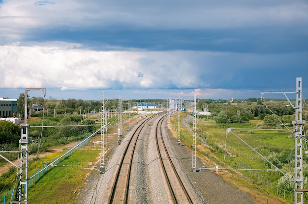 Железнодорожная линия, уходящая в горизонт на фоне облачного неба