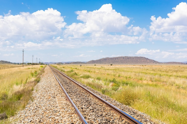 Railway in the middle of a dry grass field under the cloudy blue sky