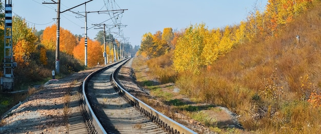 The railway passes through a beautiful autumn forest with colorful trees. the road turns, the railway background.