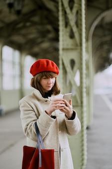 鉄道駅。美しい少女は電車を待っており、携帯電話を見ています。女性は光を旅します。