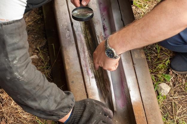線路-虫眼鏡を通して見たコンセプトイメージ。男は鉄道のレール表面を調べます。