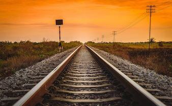 日の出時間の田園風景の鉄道線路