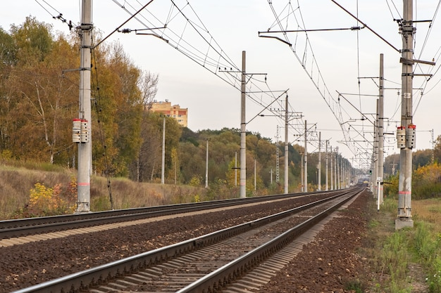 Railway track with electricity pylons in perspective view go into the horizon