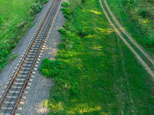 Железнодорожные пути и грунтовая дорога, вид сверху.