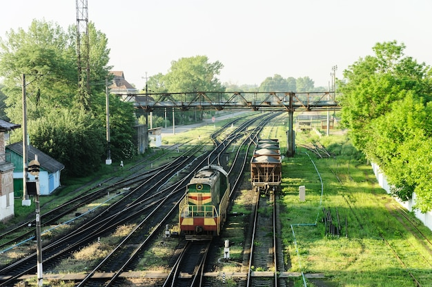 Railway tracks. top view. there is a diesel locomotive and freight wagons in the distance.