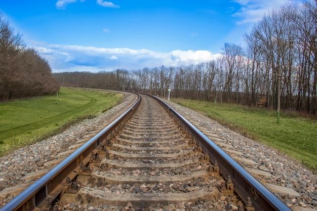 철도, 이른 봄의 기차 트랙, 맑은 흐린 날, 잎이없는 나무와 푸른 잔디