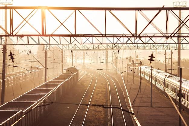 Железная дорога с грузовым и пассажирским поездом на рассвете с солнцем.