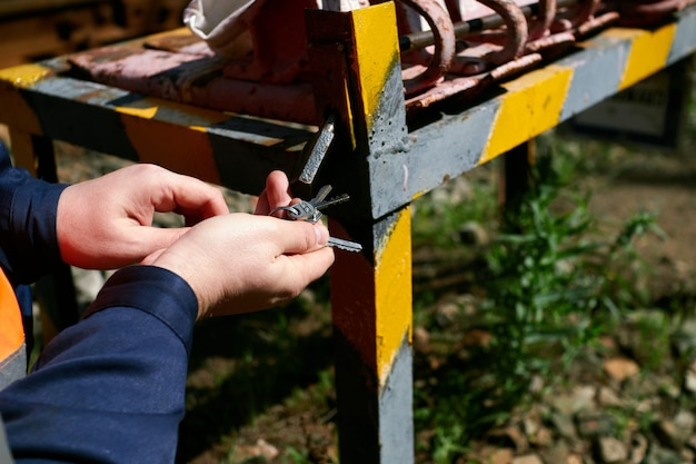 A railway worker opens the lock on a rack. the red railway brake shoe lies on the rack.