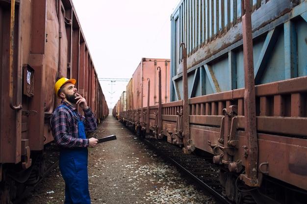 Железнодорожник осматривает грузовые контейнеры.