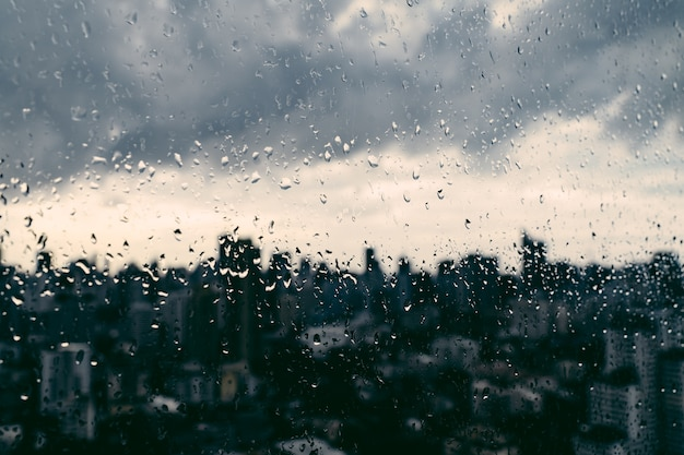 Rain over bangkok: out of focus cityscape behind the window glass with rain drops