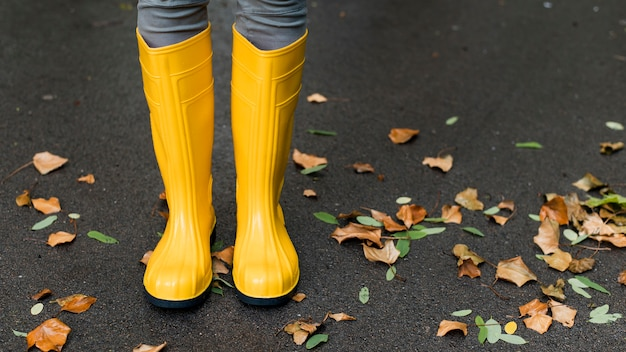 Rain boots next to autumn leaves