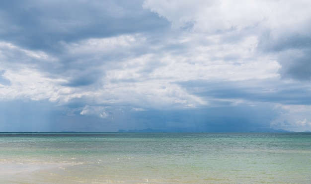 Rain clouds over beautiful tropical beach seascape in summer season